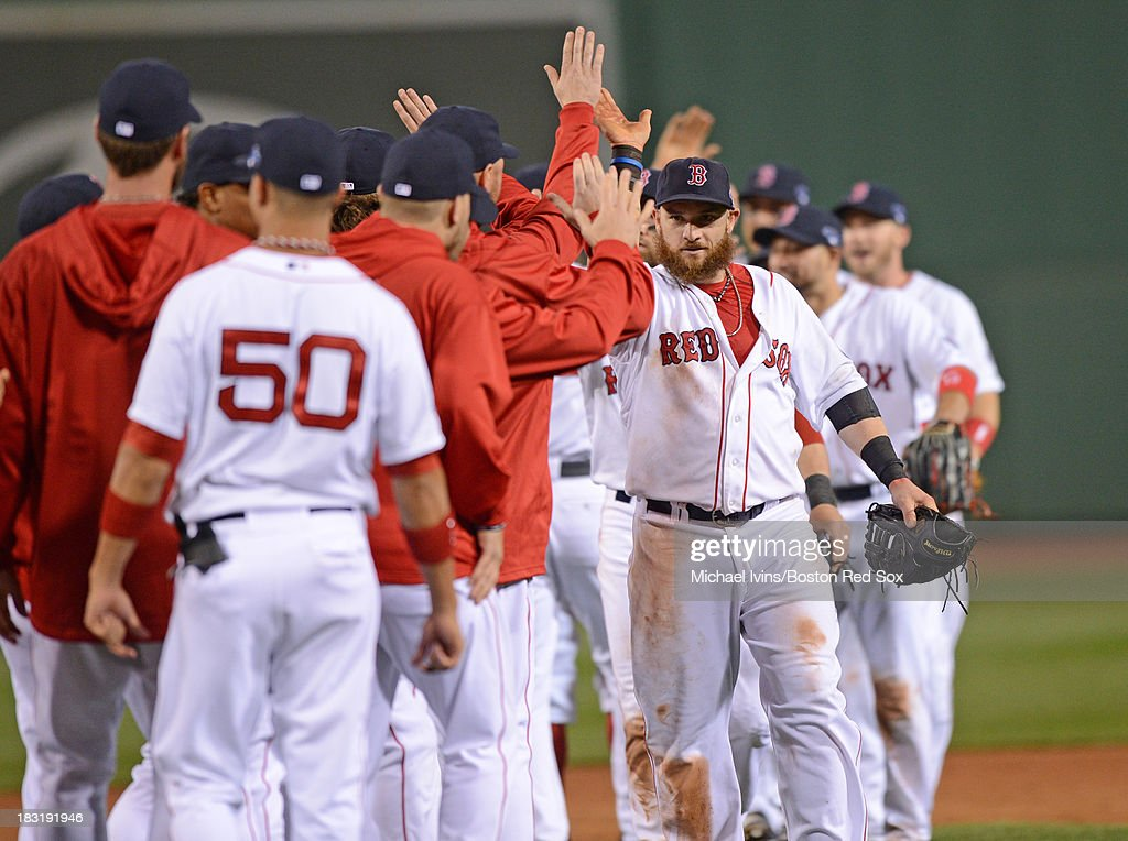 Jonny Gomes #5 of the Boston Red Sox celebrates with his team after a 7-4 victory against the Tampa Bay Rays in game two of the American League Division Series on October 5, 2013 at Fenway Park in Boston, Massachusetts.