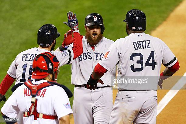 Jonny Gomes of the Boston Red Sox celebrates with teamates David Ortiz and Dustin Pedroia after hitting a three run home run to left field against...