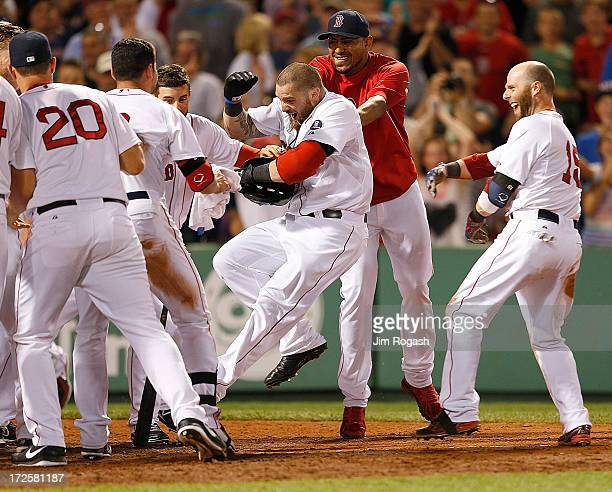 Jonny Gomes of the Boston Red Sox is mobbed after he hit a walkoff home run to give the Red Sox a 21 win against the San Diego Padres at Fenway Park...