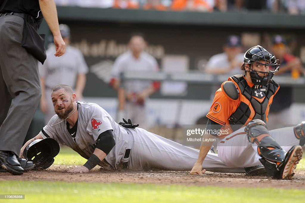 Jonny Gomes #5 of the Boston Red Sox is safe at home on a missed tag by Taylor Teagarden #31 of the Baltimore Orioles in the fourth inning during a baseball game against the Baltimore Orioles on June 15, 2013 at Oriole Park at Camden Yards in Baltimore, Maryland.