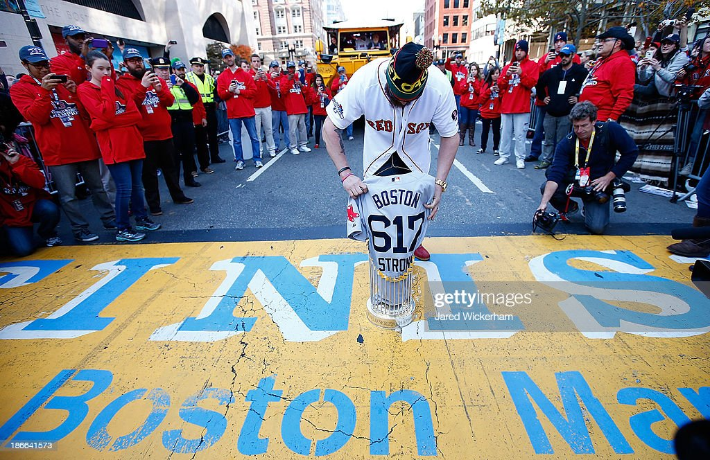 Jonny Gomes #5 of the Boston Red Sox lays the World Series trophy and the 'Boston Strong 617' jersey onto the finish line of the Boston Marathon on Boylston Street during the World Series victory parade on November 2, 2013 in Boston, Massachusetts.