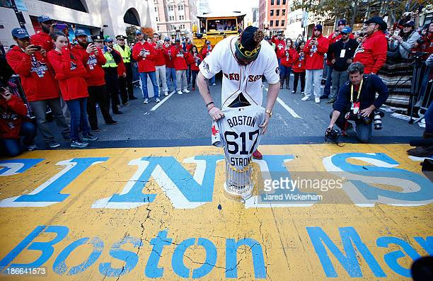 Jonny Gomes of the Boston Red Sox lays the World Series trophy and the 'Boston Strong 617' jersey onto the finish line of the Boston Marathon on...