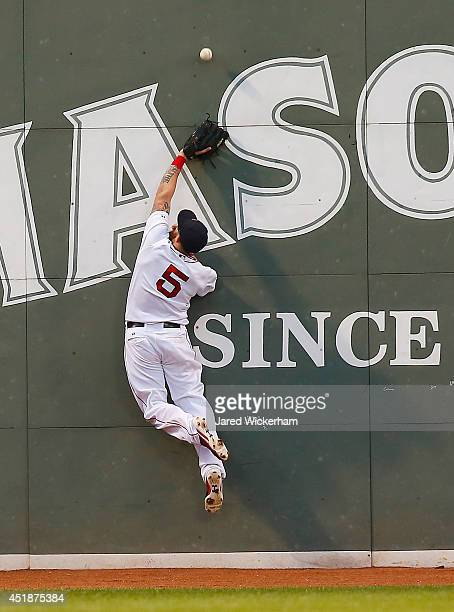 Jonny Gomes of the Boston Red Sox leaps for a fly ball in left field in front of the Green Monster but comes up short against the Chicago White Sox...