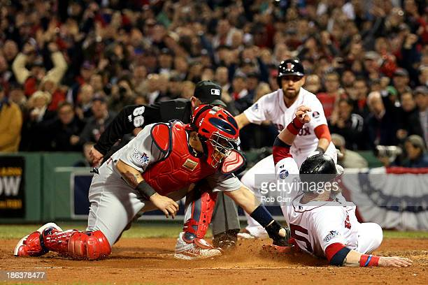 Jonny Gomes of the Boston Red Sox slides safely into home plate as Yadier Molina of the St Louis Cardinals tries to make the play during Game Six of...