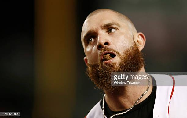 Jonny Gomes of the Boston Red Sox spits out chewing tobacco after grounding into a double play against the Baltimore Orioles at Fenway Park on August...
