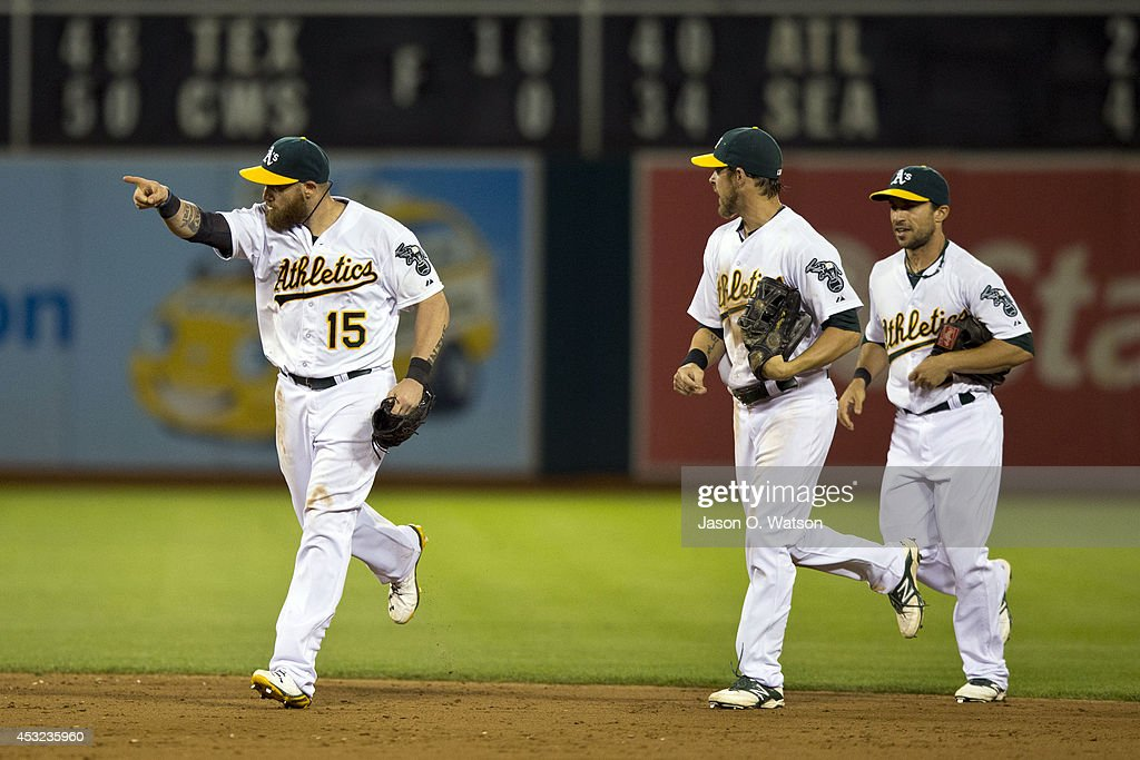 Jonny Gomes #15 of the Oakland Athletics celebrates with Josh Reddick #16 and Sam Fuld #23 after the game against the Tampa Bay Rays at O.co Coliseum on August 5, 2014 in Oakland, California. The Oakland Athletics defeated the Tampa Bay Rays 3-0.