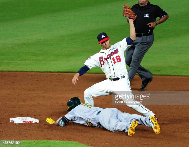 Jonny Gomes of the Oakland Athletics dives safely in to second base against Andrelton Simmons of the Atlanta Braves during the sixth inning at Turner...