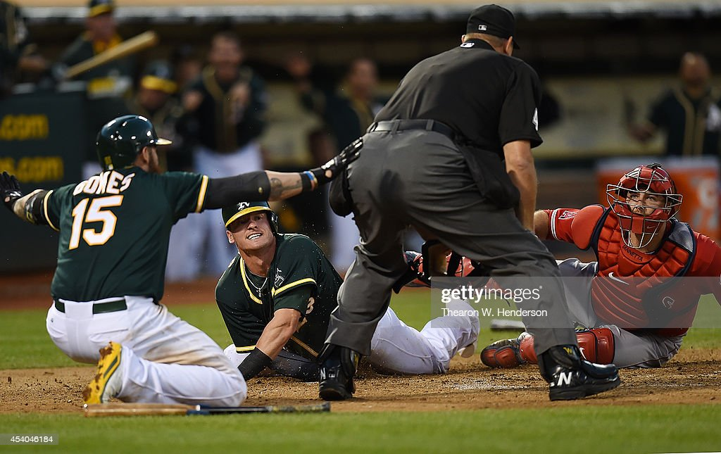 Jonny Gomes #15 of the Oakland Athletics gives the safe call after teammate Josh Donaldson #20 slid into home tagged by catcher Chris Ianntta #17 of the Los Angeles Angels of Anaheim in the bottom of the six inning at O.co Coliseum on August 23, 2014 in Oakland, California. Donaldson was called out by home plate umpire Chad Fairchild #4.
