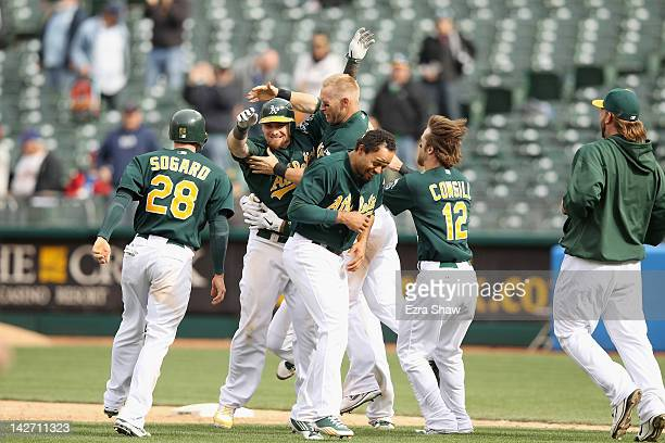 Jonny Gomes of the Oakland Athletics is congratulated by teammates after he was hit by a pitch with the bases loaded that scored the winning run in...