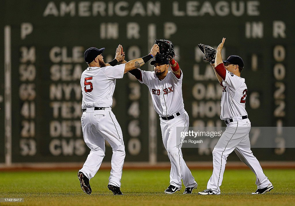 Jonny Gomes #5, Shane Victorino #18, and Daniel Nava #29 of the Boston Red Sox celebrate a win over the Tampa Bay Rays at Fenway Park on July 23, 2013 in Boston, Massachusetts.