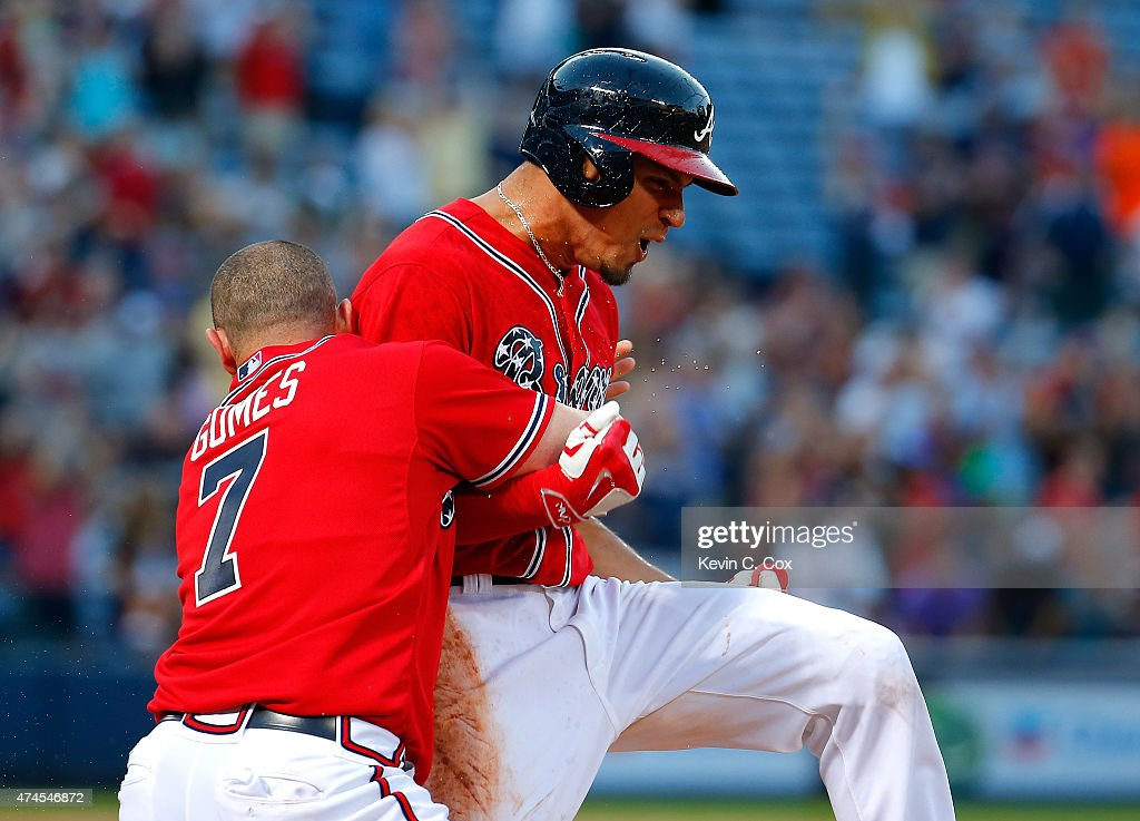 Jonny Gomes #7 tackles Jace Peterson #8 of the Atlanta Braves after he hit a walk-off RBI single in the 11th inning against the Milwaukee Brewers at Turner Field on May 23, 2015 in Atlanta, Georgia. The Braves win 3-2.