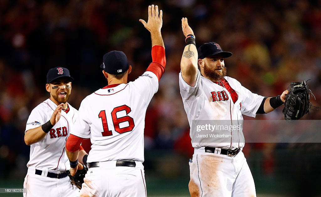 Jonny Gomes #5, Will Middlebrooks #16, and Jacoby Ellsbury #2 of the Boston Red Sox celebrate after defeating the Tampa Bay Rays 7-4 in Game Two of the American League Division Series at Fenway Park on October 5, 2013 in Boston, Massachusetts.