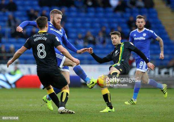 Jonny Howson and Wes Hoolahan of Norwich City are challenged by Aron Gunnarsson of Cardiff City during the Sky Bet Championship match between Cardiff...