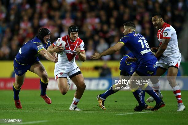 Jonny Lomax of St Helens crashes through the tackle of Chris Hill and Toby King of Warrington Wolves during the BetFred Super League semi final match...