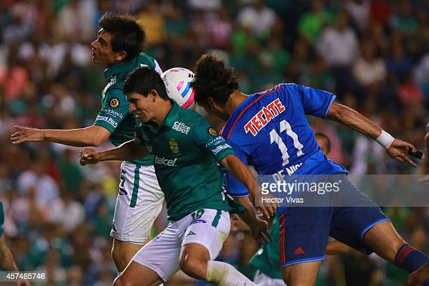 Jonny Magallon and Juan Ignacio Gonzalez of Leon struggles for the ball with Aldo de Nigris of Chivas during a match between Leon and Chivas as part...