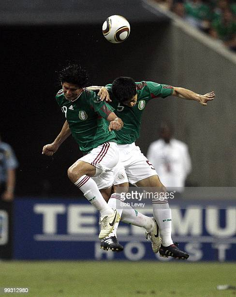 Jonny Magallon and Ricardo Osorio of Mexico go up for a header against Angola at Reliant Stadium on May 13 2010 in Houston Texas