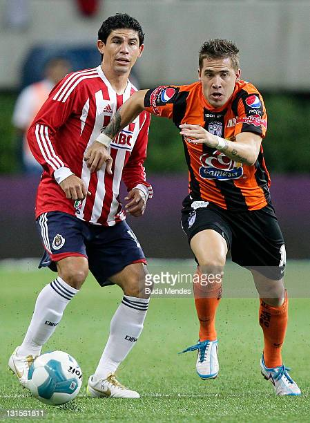 Jonny Magallon of Chivas struggles for the ball with Mauro Cejas of Pachuca during a match as part of Apertura 2011 at Omnilife stadium on November...