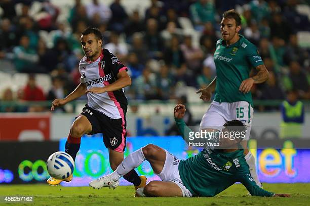 Jonny Magallon of Leon sledes to steal the ball from Maikon Souza of Atlas during a match between Leon v Atlas as part of 15th round Apertura 2014...