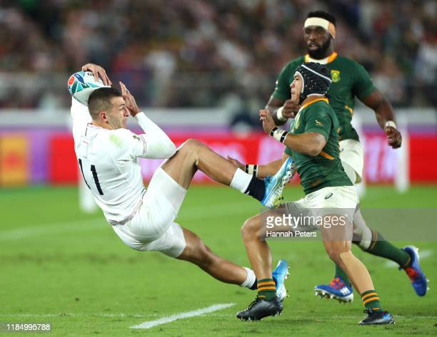Jonny May of England attempts to catch the ball under pressure from Cheslin Kolbe of South Africa during the Rugby World Cup 2019 Final between...
