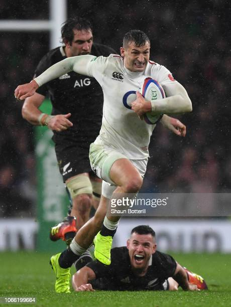 Jonny May of England avoids a tackle from Ryan Crotty of New Zealand during the Quilter International match between England and New Zealand at...