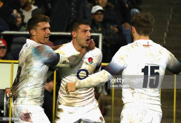 Jonny May of England celebrates with team mates Henry Slade and Elliot Daly after scoring a try during the third test match between South Africa and...