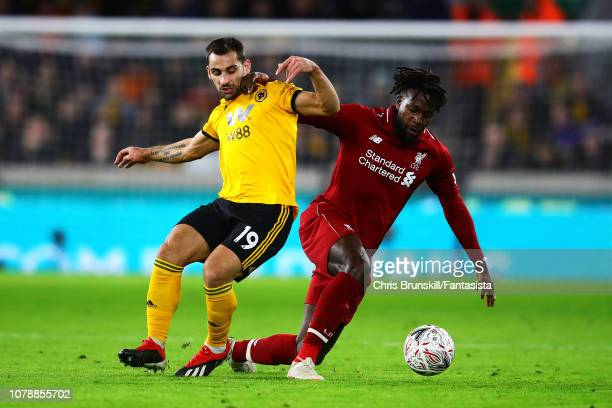 Jonny Otto of Wolverhampton Wanderers competes with Divock Origi of Liverpool during the Emirates FA Cup Third Round match between Wolverhampton...