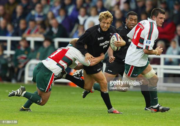 Jonny Wilkinson, of Newcastle is tackled by Neil Back during the Zurich Premiership match between Newcastle Falcons and Leicester Tigers at Kingston...