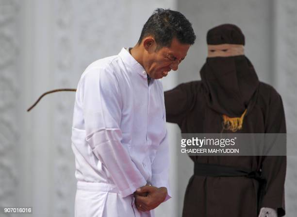 TOPSHOT Jono Simbolon an Indonesian Christian grimaces in pain as he is flogged in front of a crowd outside a mosque in Banda Aceh Aceh province on...