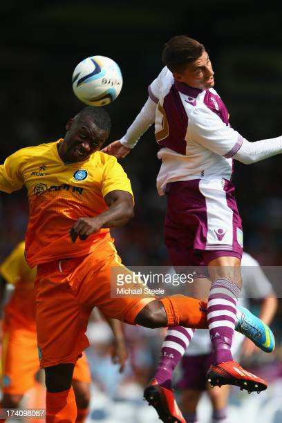 JonPaul Pittman of Wycombe Wanderers leaps alongside Matthew Lowton of Aston Villa during the Pre Season Friendly match between Wycombe Wanderers and...