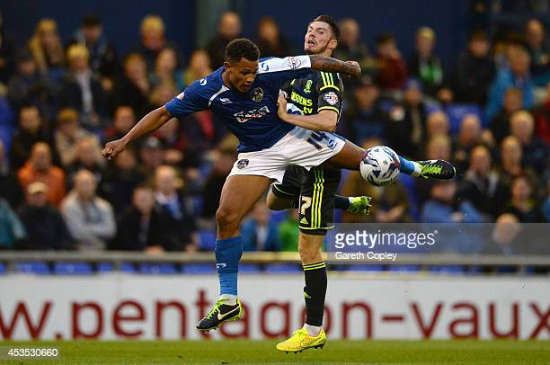 Jonson ClarkeHarris is tackled by James Husband of Middlesbrough during the Capital One Cup First Round match between Oldham Athletic and...
