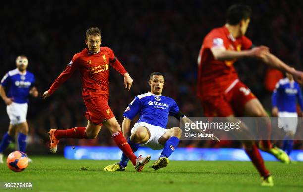 Jonson ClarkeHarris of Oldham offloads the ball as he is challenged by Lucas of Liverpool during the Budweiser FA Cup third round match between...