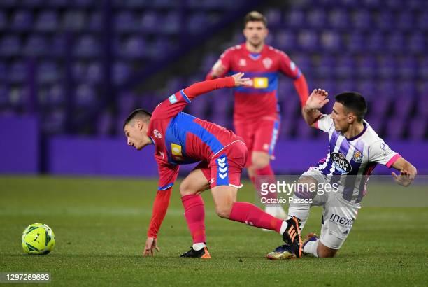 Jony Alamo of Elche CF is tackled by Fede San Emeterio of Real Valladolid during the La Liga Santander match between Real Valladolid CF and Elche CF...