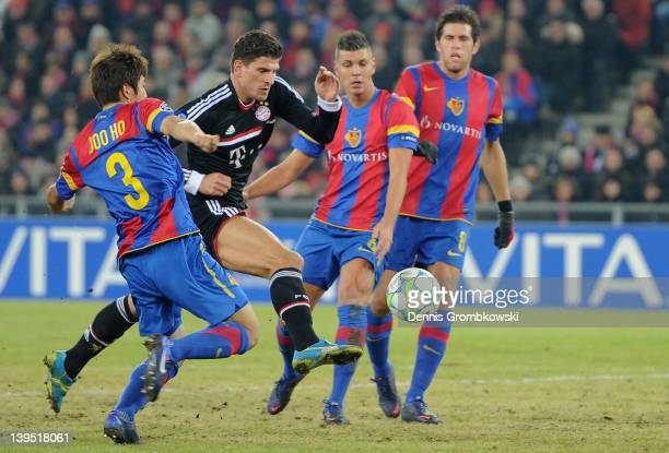 Joo Ho Park of Basel challenges Mario Gomez of Bayern during the UEFA Champions League round of sixteen first leg match between FC Basel 1893 and FC...