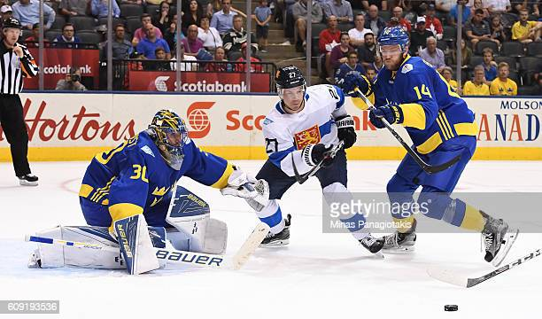 Joonas Donskoi of Team Finland and Mattias Ekholm battle for a loose puck in front of Henrik Lundqvist of Team Sweden during the World Cup of Hockey...