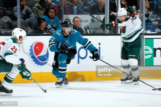 Joonas Donskoi of the San Jose Sharks reaches out for the puck as Jonas Brodin of the Minnesota Wild defends at SAP Center on April 7 2018 in San...