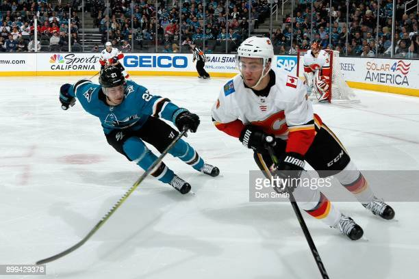 Joonas Donskoi of the San Jose Sharks skates against TJ Brodie of the Calgary Flames at SAP Center on December 28 2017 in San Jose California