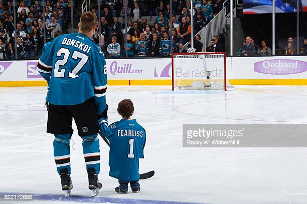 Joonas Donskoi of the San Jose Sharks stands alongside a child during the National anthem of the game against the Pittsburgh Penguins at SAP Center...