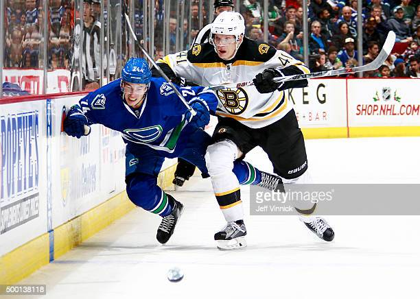 Joonas Kemppainen of the Boston Bruins checks Adam Cracknell of the Vancouver Canucks during their NHL game at Rogers Arena December 5, 2015 in...