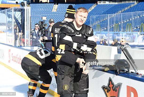 Joonas Kemppainen of the Boston Bruins takes off his jersey during practice as part of the 2016 Bridgestone NHL Classic at Gillette Stadium on...
