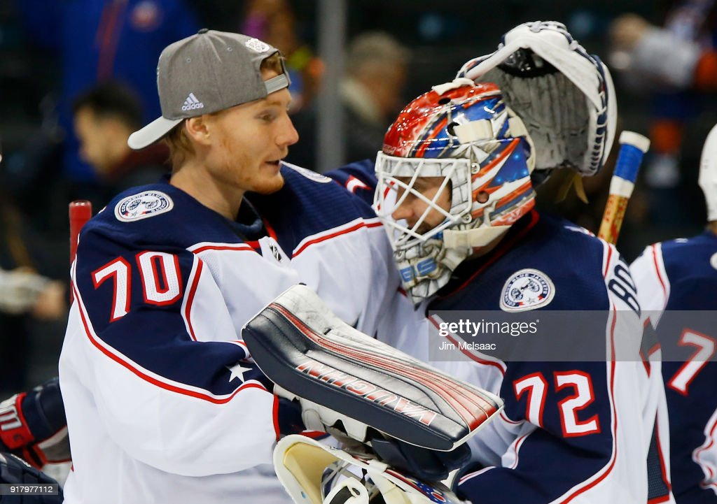 Joonas Korpisalo #70 of the Columbus Blue Jackets congratulates Sergei Bobrovsky #72 on a 4-1 win against the New York Islanders at Barclays Center on February 13, 2018 in New York City.