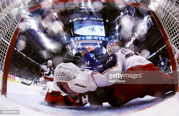 Joonas Korpisalo of the Columbus Blue Jackets makes a save on Auston Matthews of the Toronto Maple Leafs during the third period at the Air Canada...