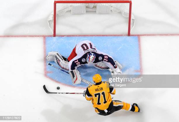Joonas Korpisalo of the Columbus Blue Jackets makes a save on Evgeni Malkin of the Pittsburgh Penguins at PPG Paints Arena on March 7 2019 in...