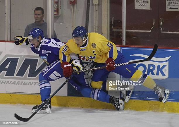 Joonas Nattinen of Team Finland is hit by Anton Lander of Team Sweden at the USA Hockey National Evaluation Camp on August 5, 2010 in Lake Placid,...