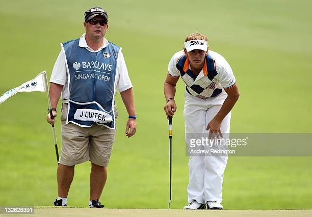 Joost Luiten of The Netherlands and his caddie Martin Gray line up a putt on the 11th hole during the final round of the Barclays Singapore Open at...