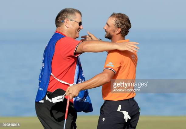 Joost Luiten of the Netherlands and his caddie Michael Waite celebrate victory on the 18th green during the final round of the NBO Oman Open at Al...