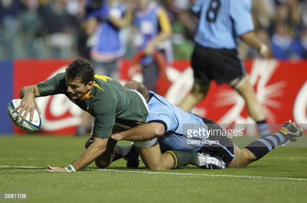 Joost van der Westhuizen scores a try despite attention from Rodrigo Sanchez for Uruguay during the Rugby World Cup Pool C match between South Africa...