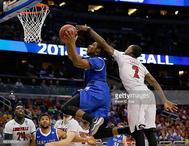 Jordair Jett of the Saint Louis Billikens goes up for a shot in front of Russ Smith of the Louisville Cardinals in the second half during the third...