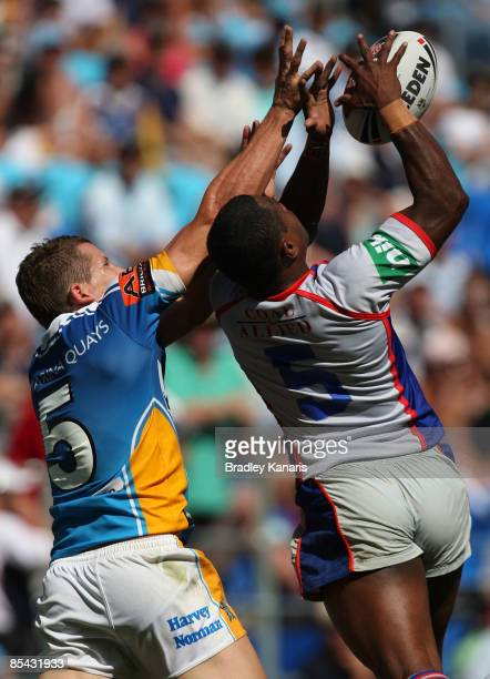 Jordan Atkins of the Titans and Akuila Uate of the Knights compete for the ball during the round one NRL match between the Gold Coast Titans and the...