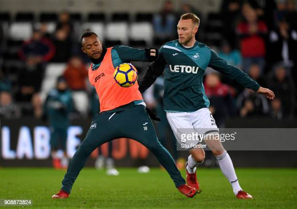 Jordan Ayew and Mike van der Hoorn of Swansea City warm up prior to the Premier League match between Swansea City and Liverpool at Liberty Stadium on...