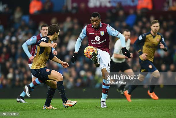 Jordan Ayew of Aston Villa controls the ball under pressure from Mathieu Flamini of Arsenal during the Barclays Premier League match between Aston...